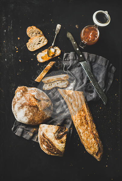 Flat-lay of baguette, bread loaf and apricot jam