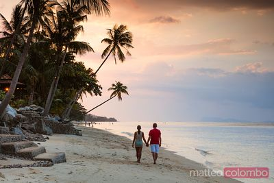 Adult couple hand in hand on beach at sunset, Thailand