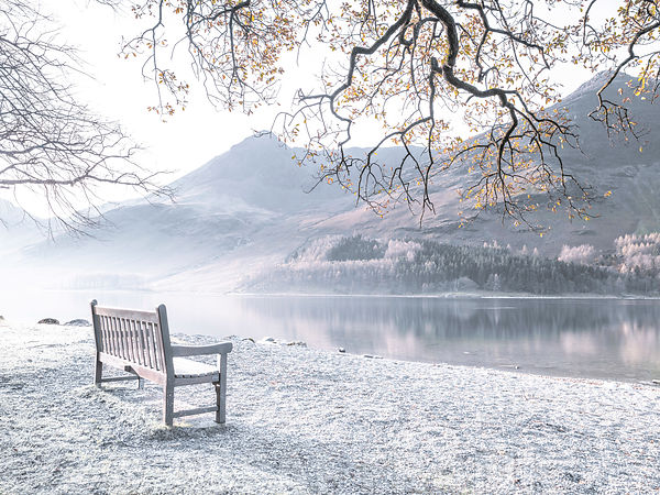 Bench and still lake, Buttermere, Lake District, UK
