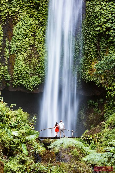 Tourist couple enjoying a waterfall in Bali, Indonesia