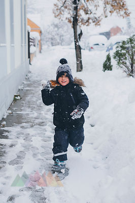 Portrait of smiling toddler throwing snowball