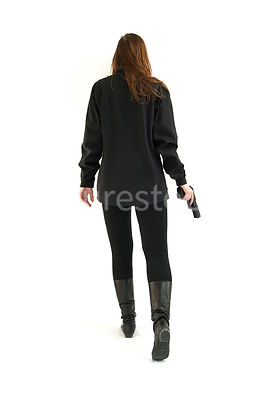 A semi-silhouette of a tough woman, holding a gun – shot from mid level.