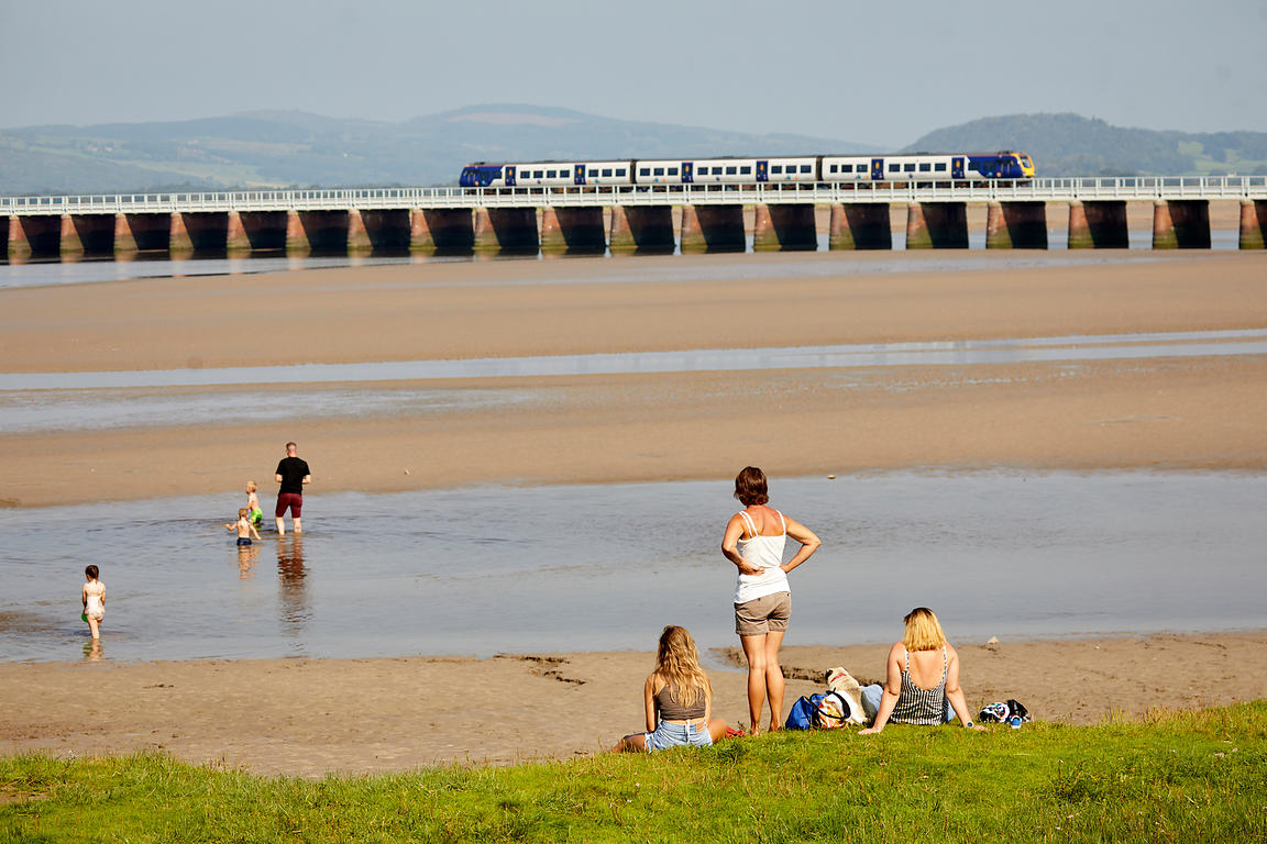 Arnside village Cumbria coastal beach Morecambe Bay,  River Kent crossed by a long viaduct structure carrying the Carnforth a...