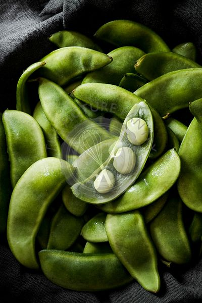 Lima beans pods sitting in a dark grey linen.
