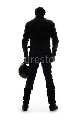 A silhouette of a mystery man in biker Leathers, standing and holding a helmet – shot from low level.
