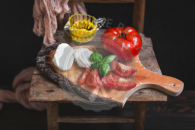 Mozzarella, tomatoes and basil on wooden serving board