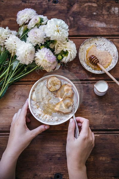 Woman eating porridge with baked pears, honey and cashew butter