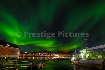 Northern Lights in the sky over the harbour with a fishing boat and jetty in Svolvær, Norway
