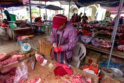 Bac Ha, Vietnam, January 7, 2020 - Butcher at Bac Ha Market saling raw meat on her wooden dark table