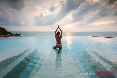 Young woman in bikini doing yoga in an infinity pool, Thailand