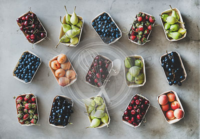 Flat-lay of various fruits and berries over grey concrete background