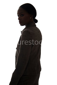 A tough woman, standing and looking around, in silhouette – shot from eye level.
