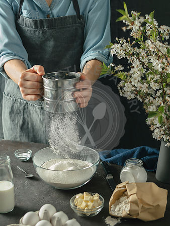 Female hands sifting flour in to mixing bow