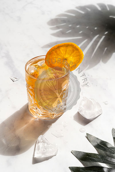 Glass with orange cocktail and ice