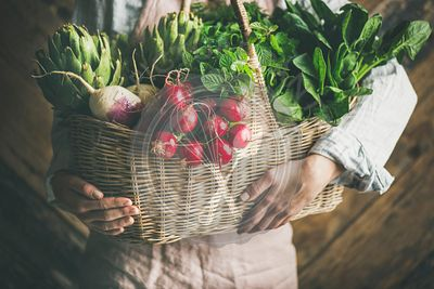 Woman farmer holding basket of organic vegetables and greens