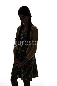 A silhouette of a 1940's girl in a dress and cardigan – shot from eye-level.