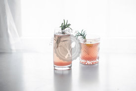 Pink grapefruit drink in two decorative glasses on a white background, garnished with rosemary.