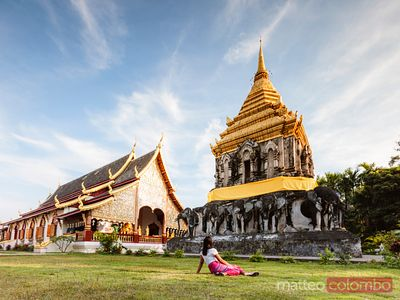Woman sitting in front of Wat Chiang Man, Chiang Mai, Thailand