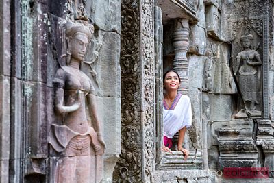 Woman sitting on a window in a temple, Angkor, Cambodia
