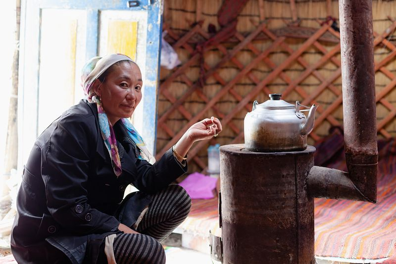 Kyrgyz woman making tea inside the yurt