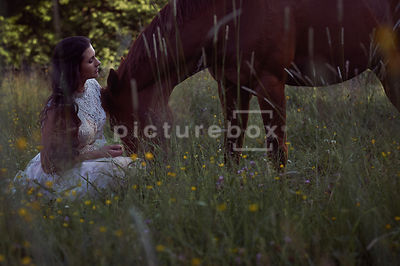 A woman in a white dress, sitting with a horse, in a meadow.