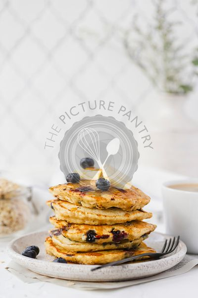 Stack of blueberry pancakes topped with maple syrup