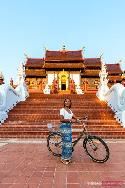 Asian woman with bicycle, in front of pagoda, Chiang Mai, Thailand