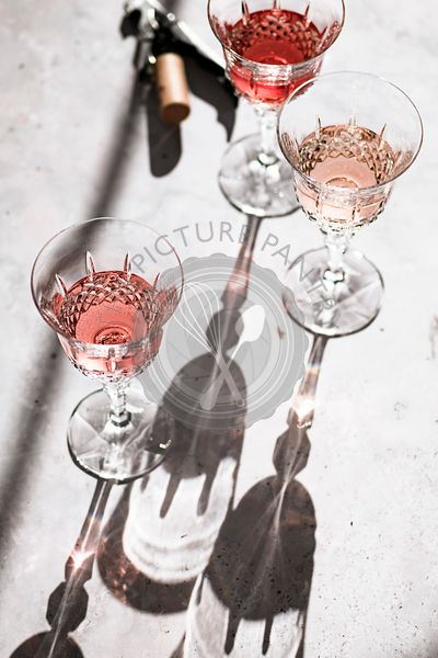 Three shades of Rosé wine in glasses casting hard shadows next to a corkscrew.