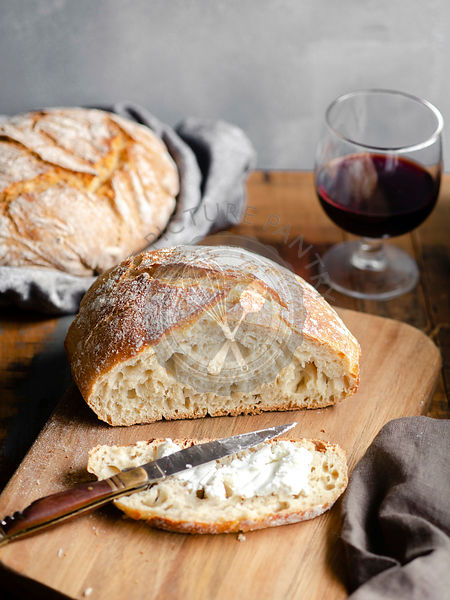 A homemade loaf of bread, sliced and buttered on a wood cutting board sitting atop a rustic table with a glass of red wine in...