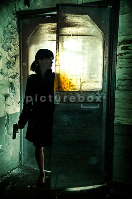 A silhouette of a mystery woman with a gun, creeping through some plastic industrial doors, inside a damp and decaying old bu...