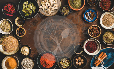 Flat-lay of spices in bowls over rusty background, copy space