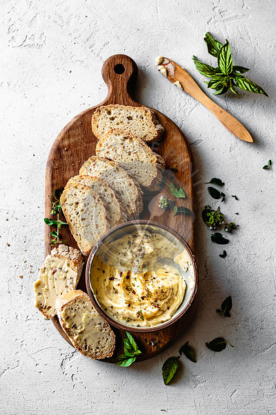 Garlic and herb butter with a sliced baguette on a wooden serving board.