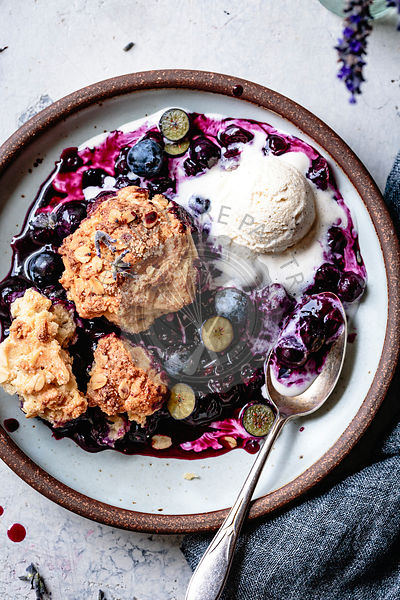 Close-up view of blueberry cobbler in a bowl with ice cream.