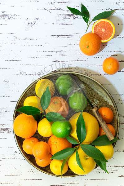 Lemons, limes, oranges and mandarins on a ceramic plate.