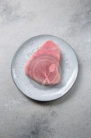 Fresh tuna steak on gray plate, gray background.