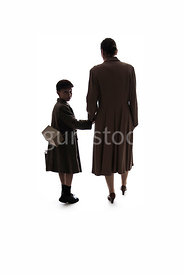 A silhouette of a 1940's woman walking with a boy – shot from eye level.