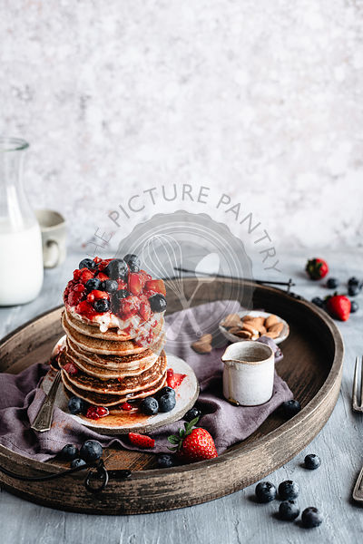 A stack of gluten free pancakes garnished with berries