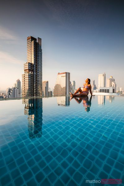 Beautiful woman in an infinity pool overlooking the skyline of Bangkok