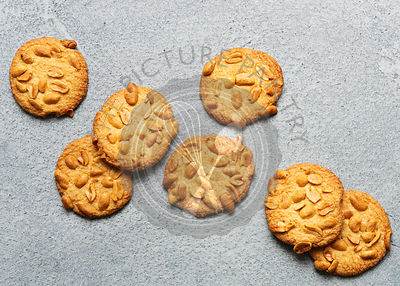 Scattered peanut biscuits against a blue background.