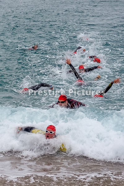 Ironman triathlon competitors wearing red hats coming in to the shore after their swim