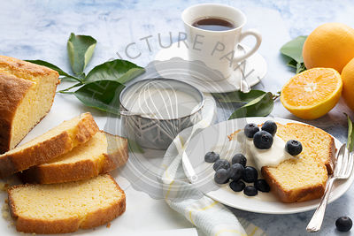 Cup of coffee and slices of orange cake topped with blueberries and cream.