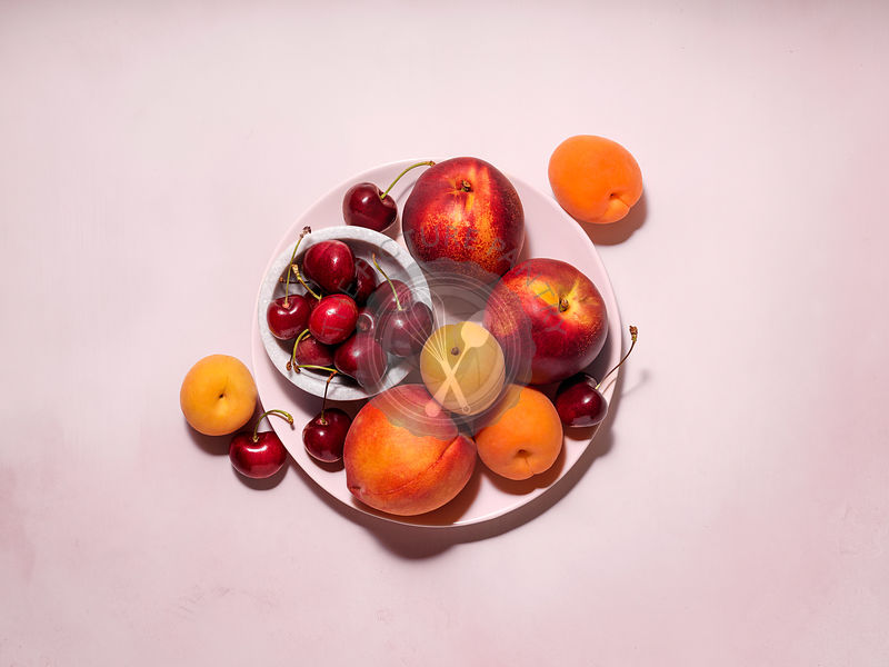 A plate filled with a variety of summer fruit (apricots, cherries, peaches, nectarines). Pale pink plate on a pale pink table...