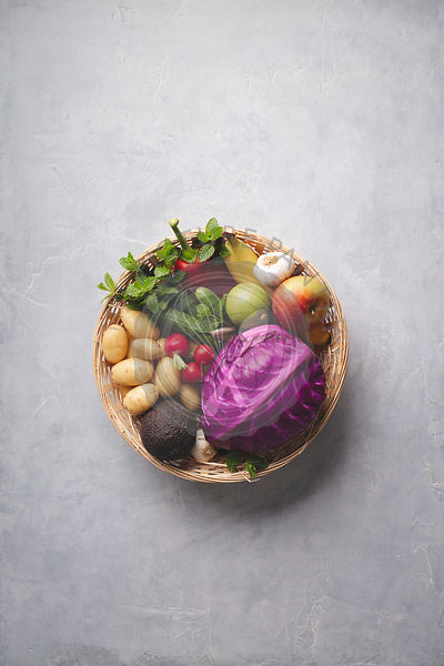 Basket of fresh organic fruits and vegetables on concrete background, flat lay