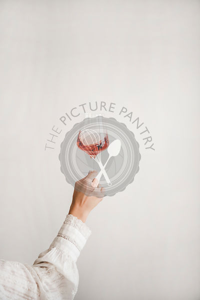 Womans hand holding glass of rose wine