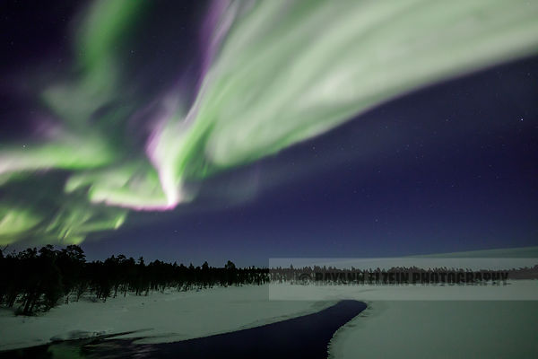 Aurora borealis dancing above a frozen river in Inari in the north of Finnish Lapland