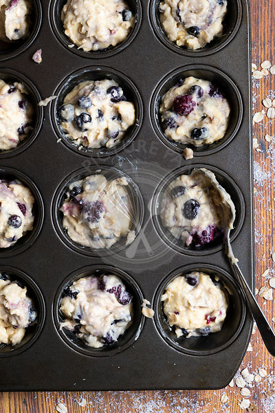 Mixed berry and oat muffin batter spooned into a patty cake pan.