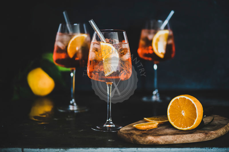 Aperol Spritz cocktail in glass with fresh oranges, black background