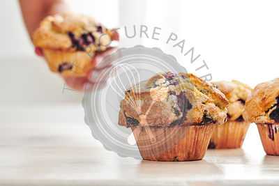 Rustic blueberry muffins on a white, wood table with bright window light in the background. A woman's hand grabs a muffin off...