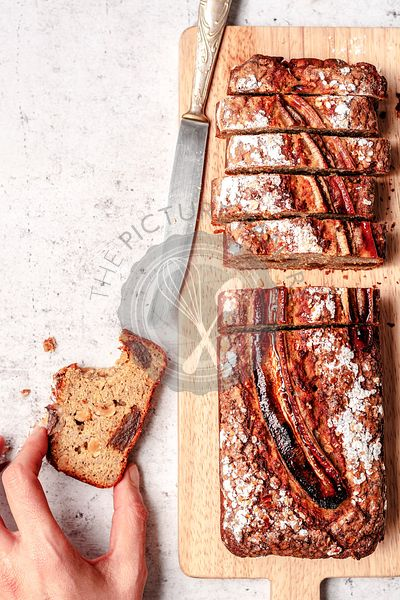 Whole grain banana bread with wallnuts and dried dates, sliced and served on a wooden cutting board with a hand grabbing one ...