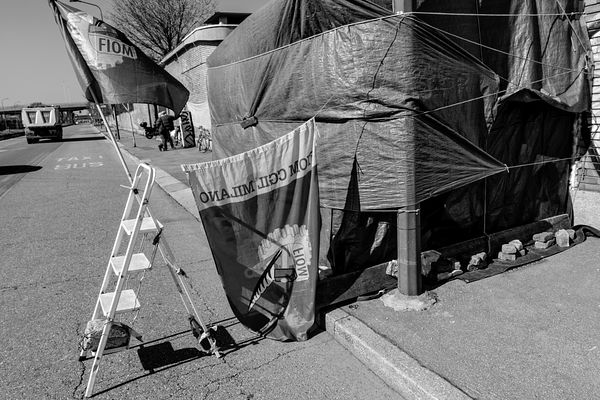 Metal workers' union flags attached to the tarpaulin shelter.